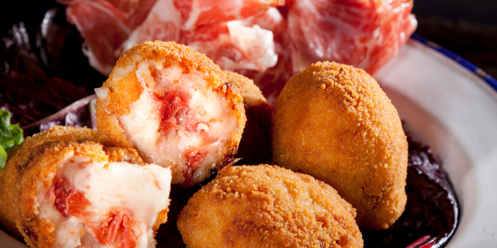 Croquetas de Jamon with Spanish Jamon on a plate.