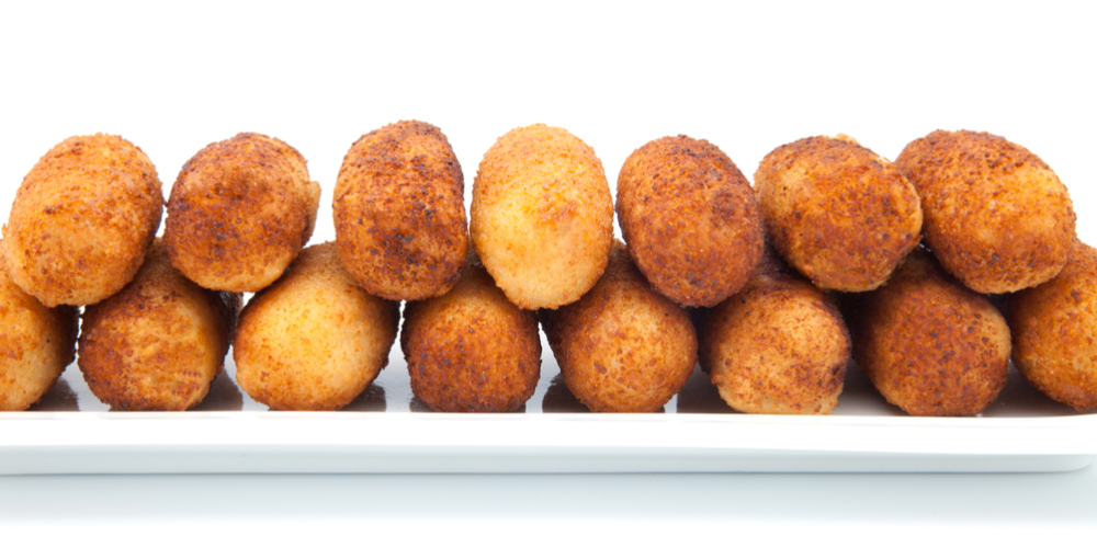 Croquetas de Tocino y Arroz stacked on white plate