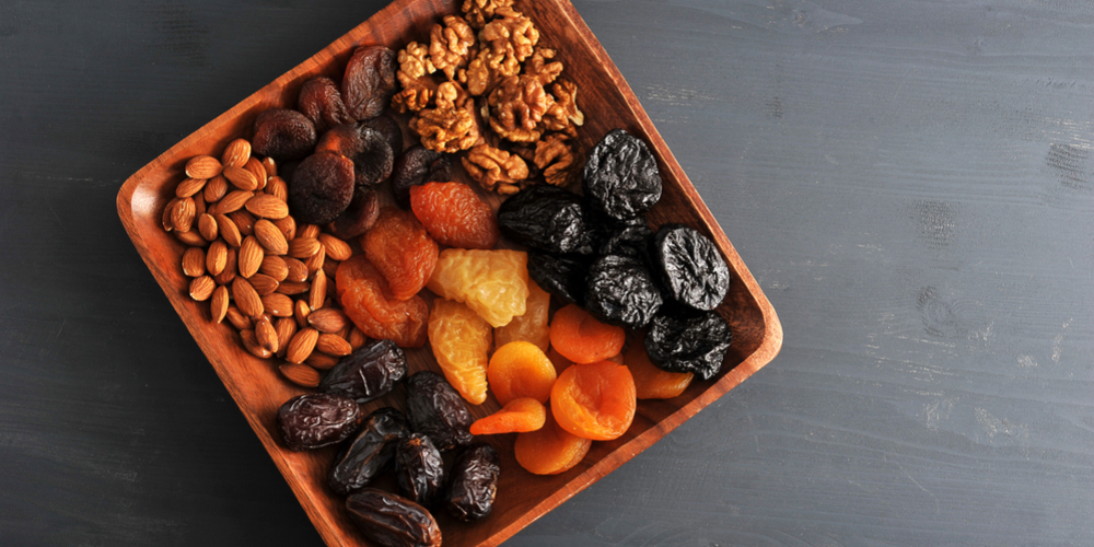 Dried fruits and nuts in wooden bowl on table
