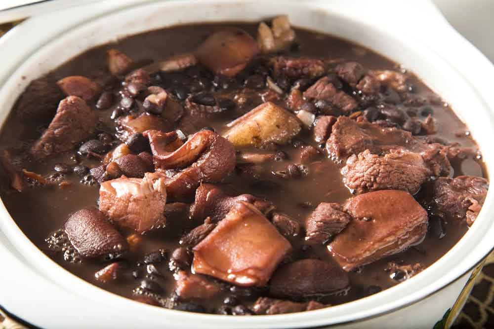 White pot filled with Brazilian National dish of Feijoada