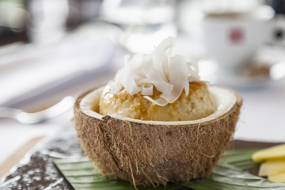 Coconut Flan served in a coconut husk with coconut shavings on top