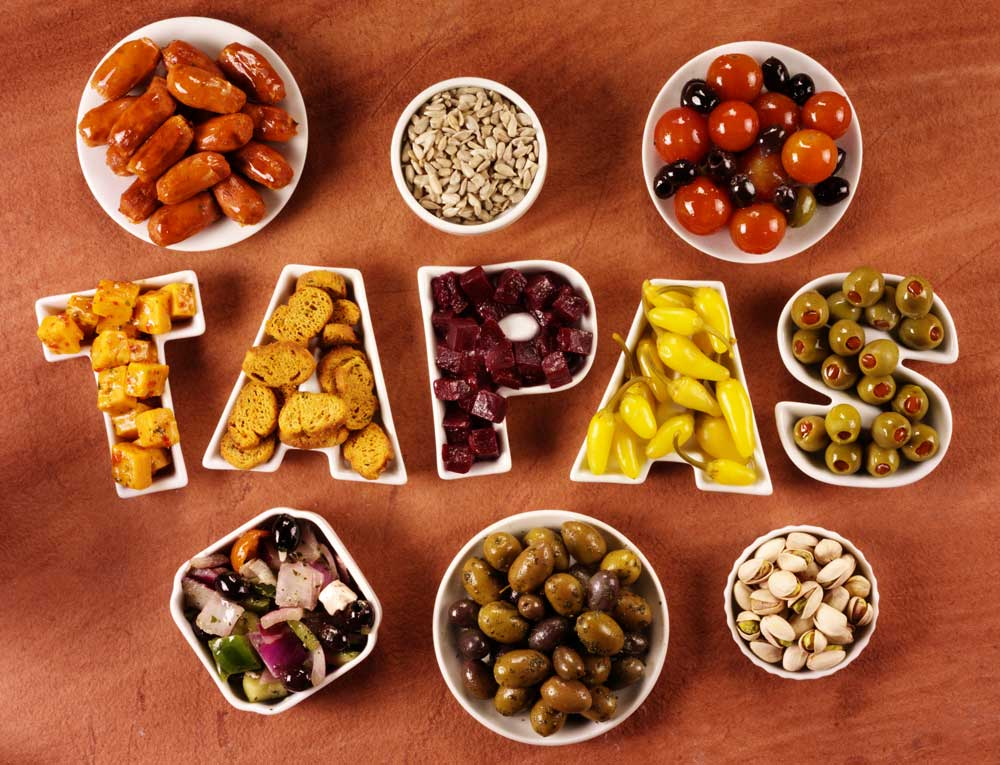 Various dishes spelling the word tapas