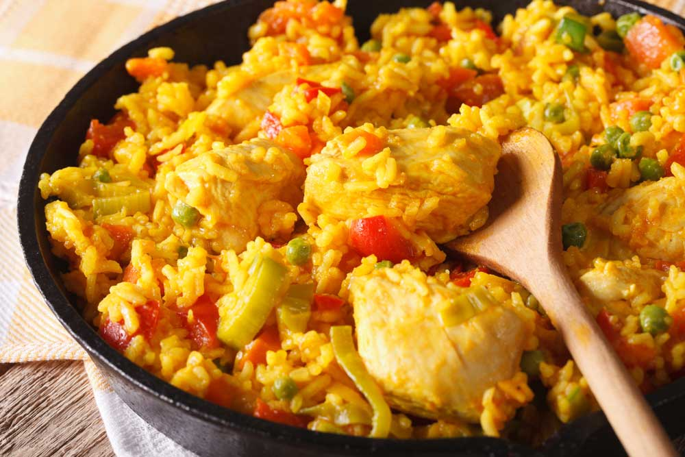 Arroz con pollo served in a dish with wooden spoon