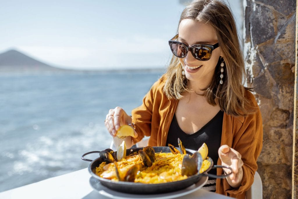 Woman eating Spanish paella on Spanish coast