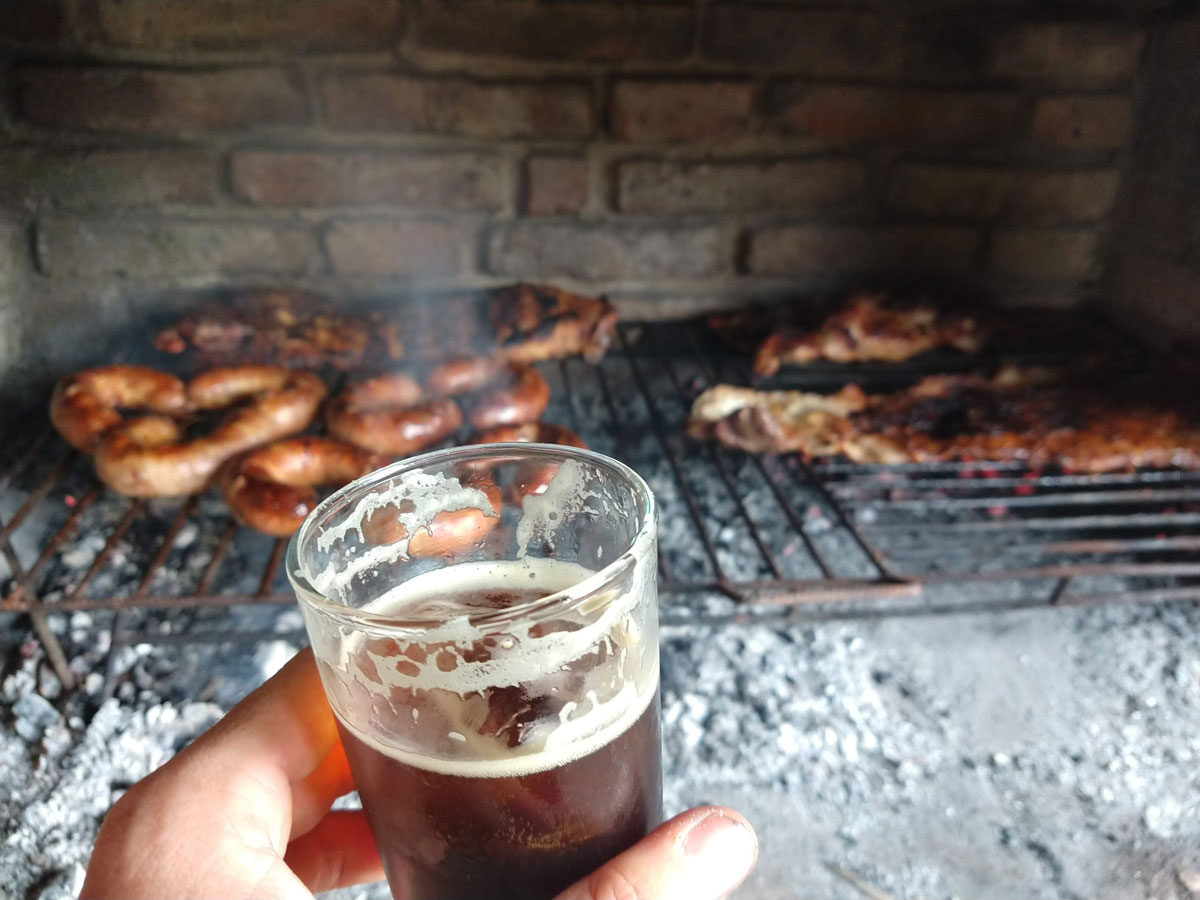 Fernet con Cola with a background of Argentinian aside bbq