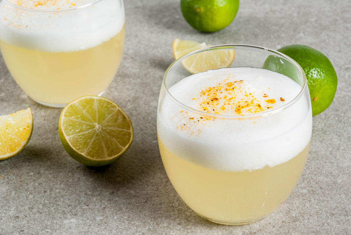 South American cocktail Pisco Sour with limes on a granite table