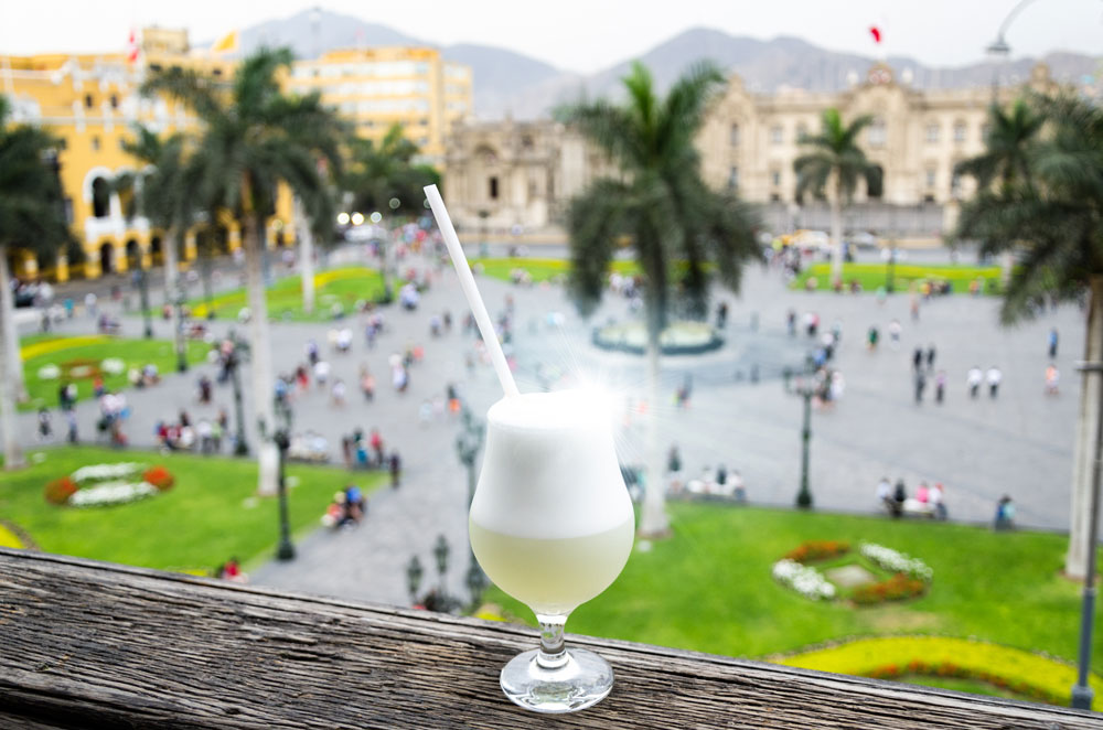 Pisco sour homemade cocktail with the background of the main square of Lima - Peru