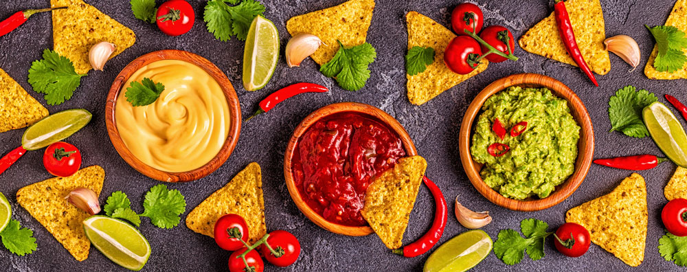 Chips and lime wedges with bowls filled with queso, salsa and guacamole