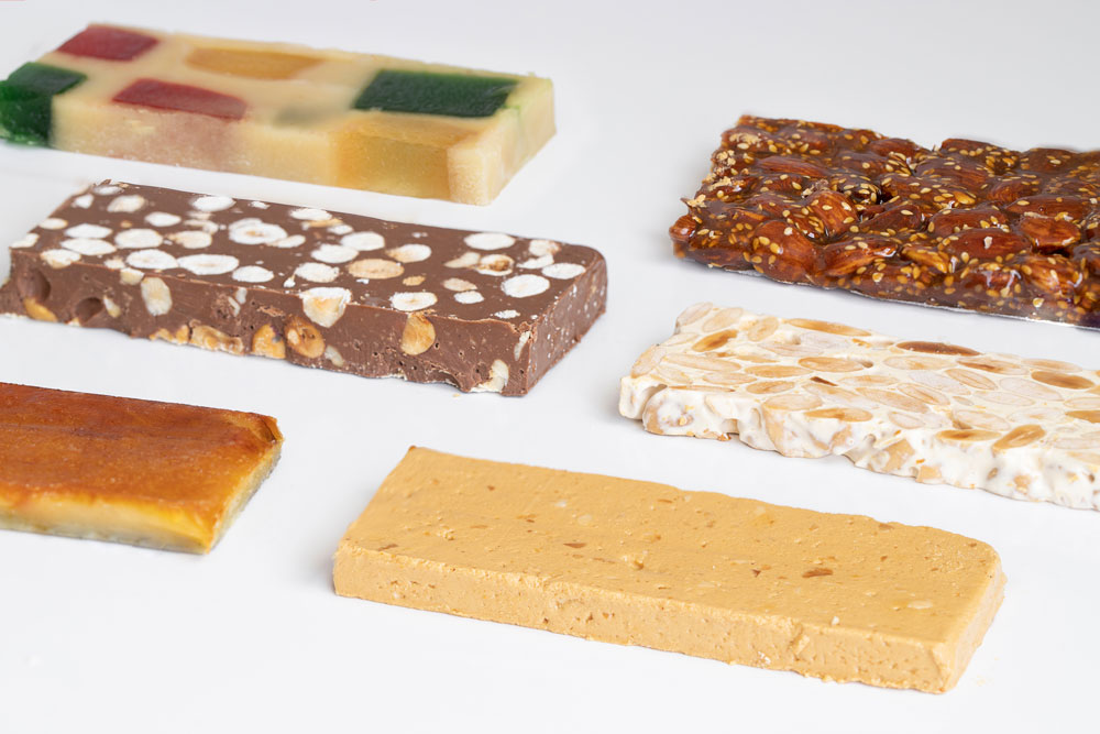 Assorted flavors of turrón on white background