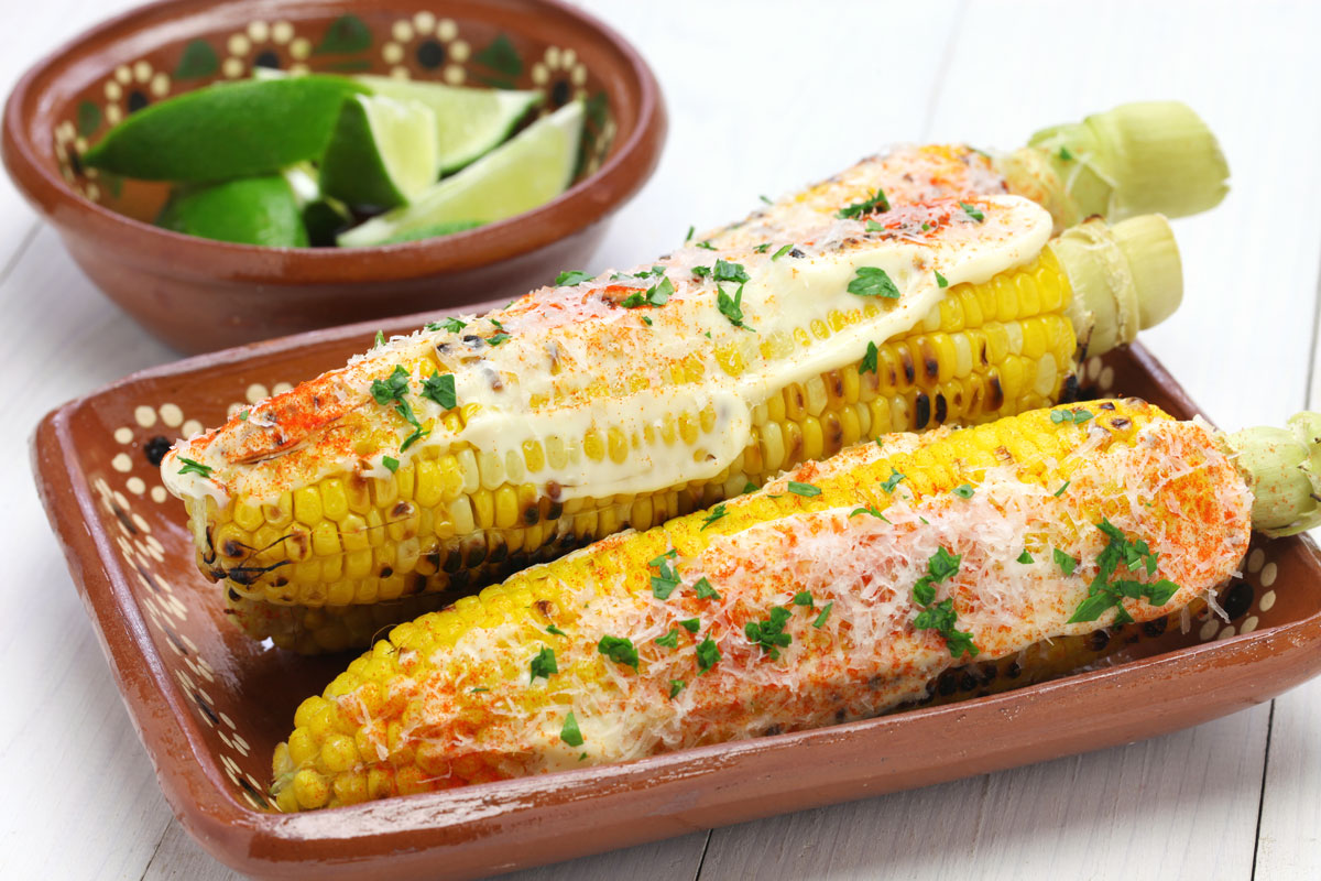 Elote Mexican Street Corn served in a paltter with lime wedges