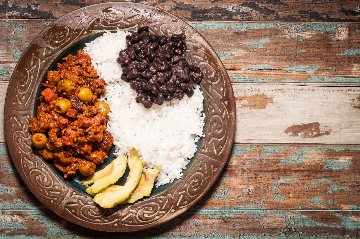 Classic Cuban Picadillo served with white rice, black beans and avocado